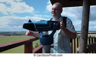 Tourist using binoculars on view tower