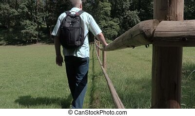Tourist goes along the wooden fence