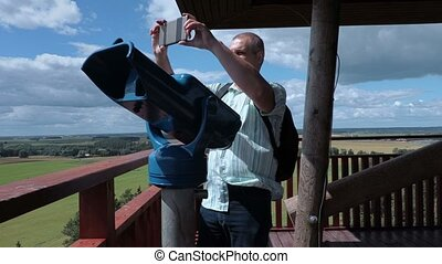 Tourist take pictures on view tower near binoculars