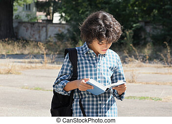 School time - A handsome schoolboy with curly hair is...