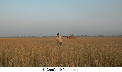 Run adult cheerful man on a wheat field. A man on the field...