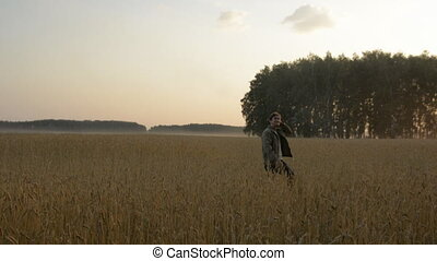 An adult man walks the wheat field. Successful farmer in...