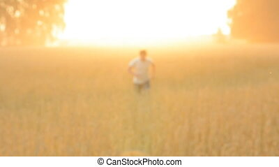 Run a cheerful farmer on the wheat field. Adult man on the...