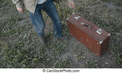 Close-up on top of a walking man with an old suitcase. Boots...