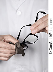 optician man cleaning a pair of eyeglasses - closeup of a...
