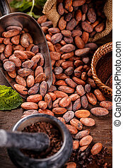 Cocoa beans and mortar with pestle on wooden background