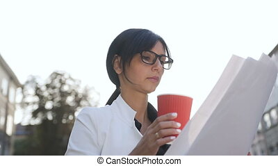A young woman wearing glasses goes to work in the morning,drinks coffee and examines documents