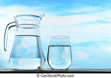 Fresh and clean drinking water in jug and glass on sky...