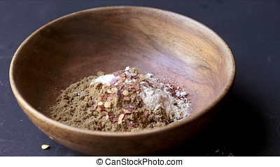 Mixing Spices - Mixing taco seasoning spices in wooden bowl