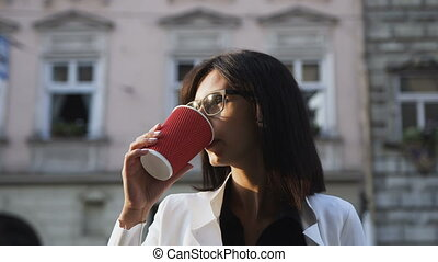 A beautiful young woman wearing glasses in the morning goes to the city and drinks coffee