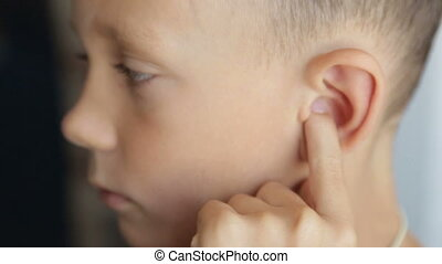 The boy's finger massages the left ear - Child's face on the...