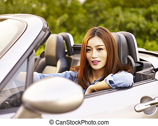young asian woman riding in a sports car - young asian woman...