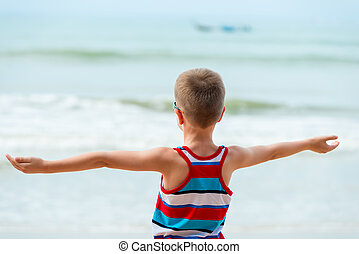 boy on the sea with outstretched hands in the hand rests