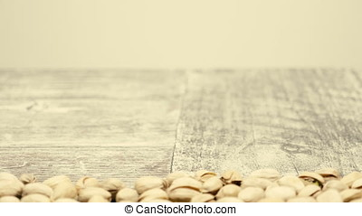 Revealing Pistachios on wooden background with copyspace in...