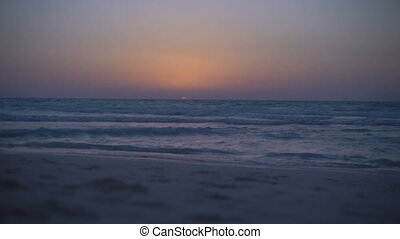 Amazing mystical sunset on the sea. Clear sky. The calm sea with small waves. Waves rippling over sand. View from the beach to horizon. Sun sets over the sea