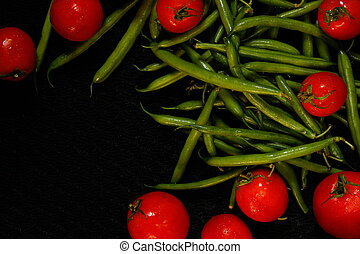 Tomatoes and asparagus on a black surface - Vegetables,...