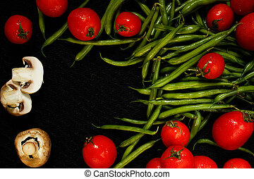 Tomatoes champignon and asparagus on a black surface -...