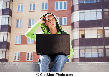 Young man using laptop on city street