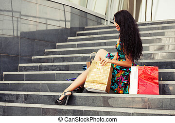 Happy young fashion woman with shopping bags sitting on mall...