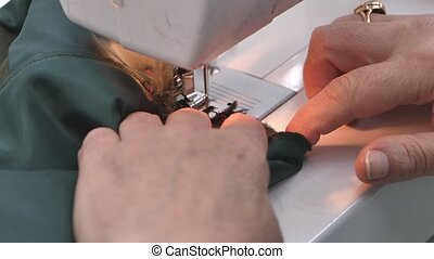 Close up footage of a professional woman tailor sewing a cotton clothes with a sewing machine.