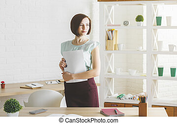 Young woman doing paperwork in modern office. Expertise and...