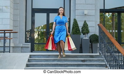 Young happy woman with shopping bags walking out from shop