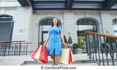 Young happy woman with shopping bags walking out from shop -...