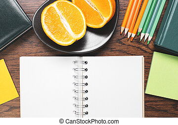 Empty notepad and fruit on desk top - Top view of wooden...