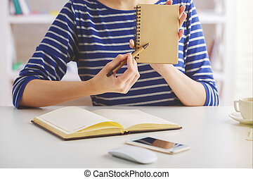 Woman showing blank notepad - Woman in striped blue shirt...
