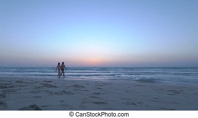 Young couple is holding hands and walks on the sandy beach at dusk. Happy woman in bikini with boyfriend is walking near the sea, along ocean. Sexy girl with husband is going on wet sand