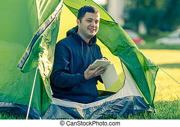 Man is sitting in a tent with a tablet
