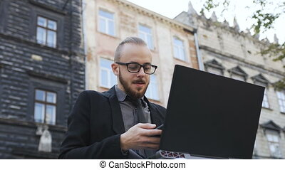A man in glasses with a phone in his hands runs on a laptop in the open air