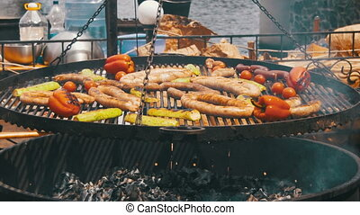 Cooking Barbecue Delicious Sausages and Vegetables on the...
