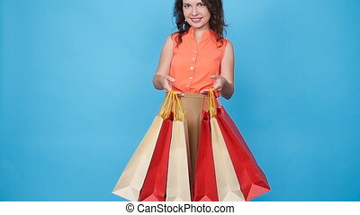 Happy young woman carrying shopping bags