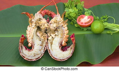 Fried lobster on the table on banana leaf with vegetables...