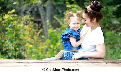 Mom and daughter hug and kiss in the park. - Mother and...
