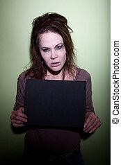 Woman taking mugshot - woman with messy hair takes mugshot