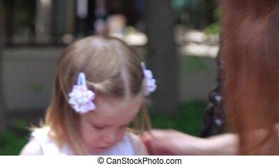 Little girl straightens her hair - On the swing little girl...