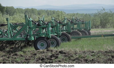 THE PLOW IS PLOWING A FIELD . the land of grass. wheels. close-up
