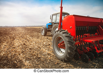 Modern tractor in the field with sowing complex.
