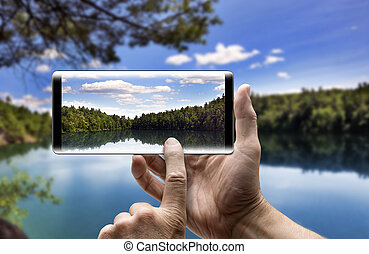 Holding a mobile Smartphone and take a picture - Two hands...