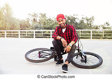 Attractive dark skinned boy sitting on his bicycle - Photo...