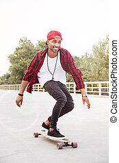 Young dark skinned man skateboarding - Photo of young dark...