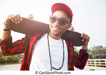 Young dark skinned man wearing sunglasses holding skateboard...