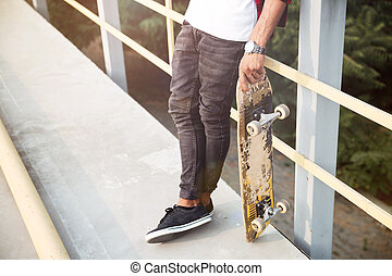 Cropped photo of young dark skinned man holding skateboard -...