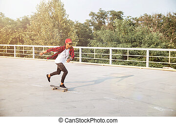 Attractive dark skinned man skateboarding - Photo of young...