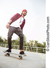 Attractive dark skinned man skateboarding - Picture of young...