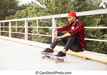 Young dark skinned man sitting with his skateboard - Picture...