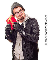 Warmly Dressed Young Man Holding Wrapped Gift To His Ear