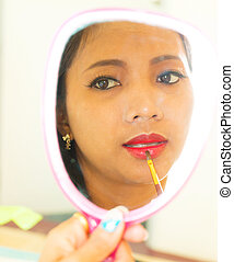 Applying Lip Gloss In Mirror Shows Beauty